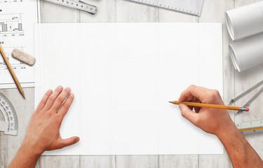 Projekt crtanja na praznom bijelom papiru. Scena odozgo s arhitektonskom opremom raspoređenom oko papira.