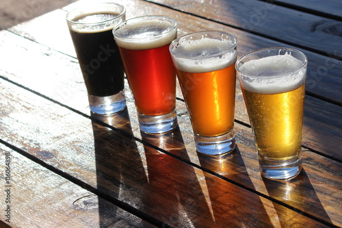 Fotografering  A selection of four craft beers during a tasting session on a wooden table