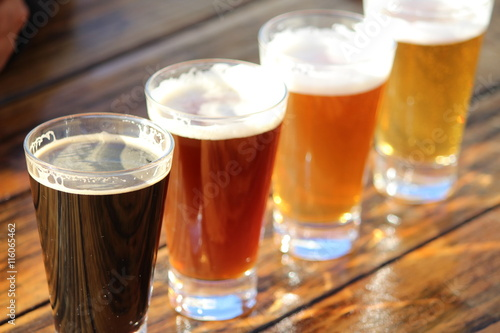 Photo A selection of four craft beers during a tasting session on a wooden table