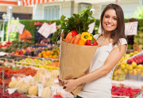 Fotografia Woman holding a bag of vegetable in a outdoor market