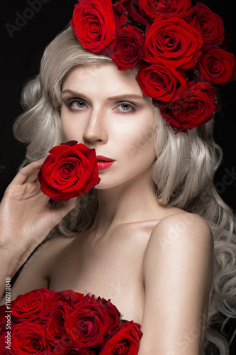 Foto  Beautiful blond girl in dress and hat with roses, classic makeup, curls, red lips