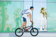 Extreme sport. Healthy active lifestyle concept. Young bike rider wearing sunglasses and snapback riding his BMX, performing tricks against a building with reflective glass wall. Motion blur