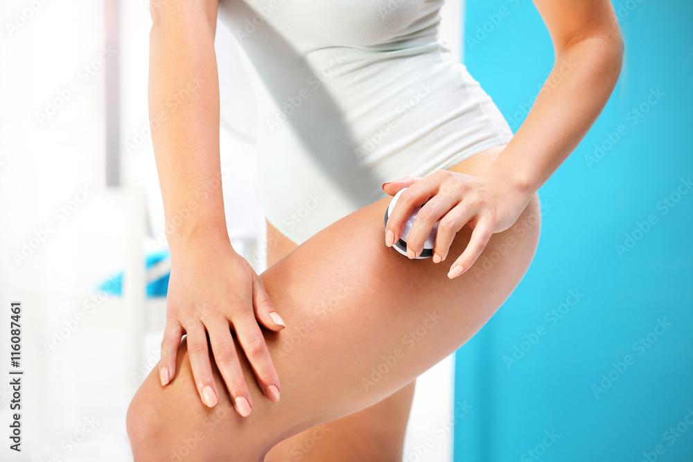 Fototapeta Masaż antycellulitowy. Kobieta masuje w łazience udo kulką do masażu.