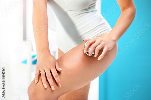 Fototapeta Masaż antycellulitowy. Kobieta masuje w łazience udo kulką do masażu.  obraz