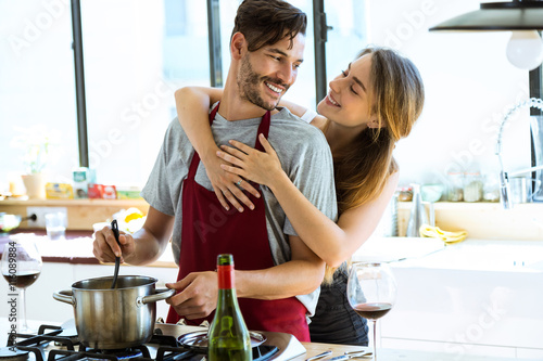 Fototapeta Happy young couple cooking together in the kitchen at home. obraz