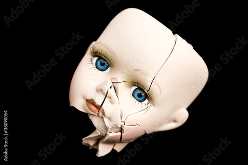 Photographie  Broken Doll Face and Head on Black Background