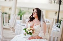 Big Breasts Brunette Bride With Wedding Bouquet Sitting On Chair
