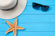 Straw hat and sunglasses on wood