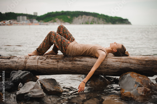 Dreaming young woman is lying on the log at the water
