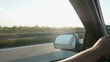 Driving in the late afternoon on a busy freeway, close-up of the side view mirror.