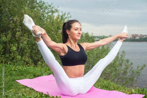 Valokuva  Woman holding legs apart doing exercises aerobics warming up with gymnastics for flexibility leg stretching workout outdoors