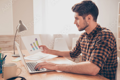 Valokuva  Side view of concentrated young man working with laptop and diag