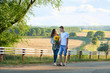 happy couple with sunflowers having fun and walking along country road outdoors - romantic travel, hiking, tourism and people concept