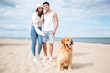 Couple hugging and walking with dog on the beach