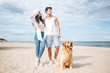 Couple walking with dog on the beach in summer