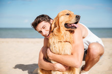 Cheerful Young Man Hugging His Dog On The Beach