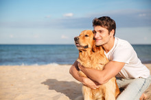 Smiling Man Hugging His Dog On The Beach In Summer