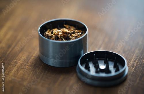 Obraz na plátne close up of marijuana or tobacco and herb grinder