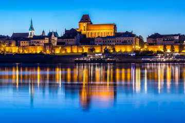 Torun Old Town at night reflected in Vistula river, Poland