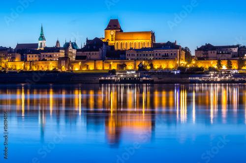 Fotografia Torun Old Town at night reflected in Vistula river, Poland