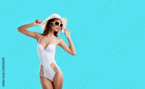 Obraz Attractive girl in a white bikini, hat, sunglasses, emotionally opened mouth on a bright blue background with a perfect body. Isolated. Studio shot. - fototapety do salonu