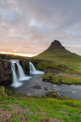 Amazing top of Kirkjufellsfoss waterfall with Kirkjufell mountain in the background on the north coast of Iceland's Snaefellsnes peninsula taken white a long shutter speed.