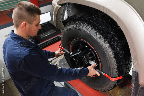 Mechanic tuning aligner for wheel alignment in garage closeup Canvas Print