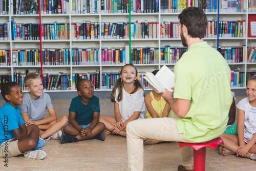 Teacher teaching kids in library Poster