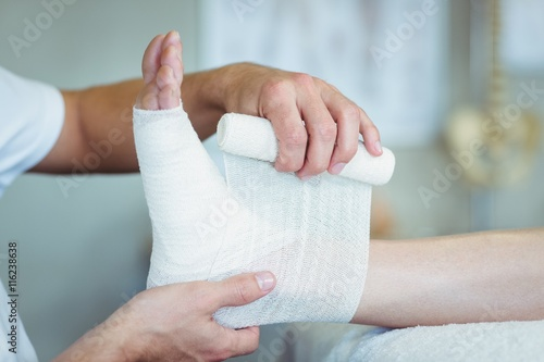 Fotografering Physiotherapist putting bandage on injured feet of patient