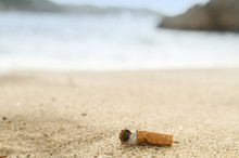 Cigarette Butts In The Sand On...