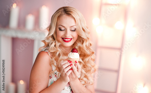 Photo  Smiling blonde woman holding birthday cake in room over lights background
