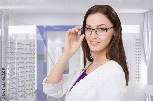 Fotografía  Portrait of young businesswoman smiling in eyeglasses at optik store