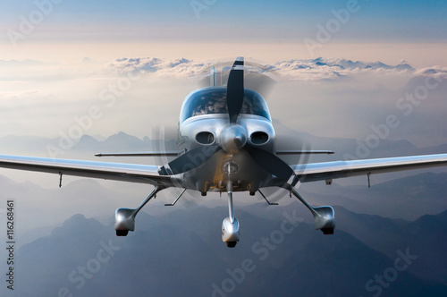Leinwand Poster Privat plane or aircraft flight surrounded by mountains and rocks