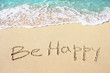 Be happy handwritten with soft ocean wave on the sandy beach
