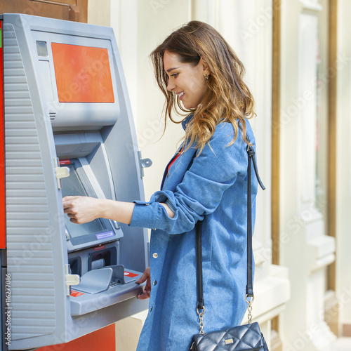 Fototapeta Happy brunette woman withdrawing money from credit card at ATM