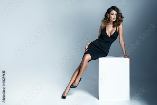 Obraz Photo of a sexy brunette woman wearing black dress - fototapety do salonu