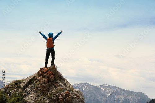 Photo cheering successful woman backpacker open arms on mountain peak