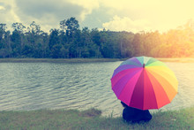 Beautiful Woman Holding Multicolored Umbrella Sitting On Green Grass With Lake Clouds And Blue Sky.Vintage Tone. Vacation Concept. Copy Space