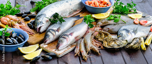 Raw seafood on wooden table. Fototapeta