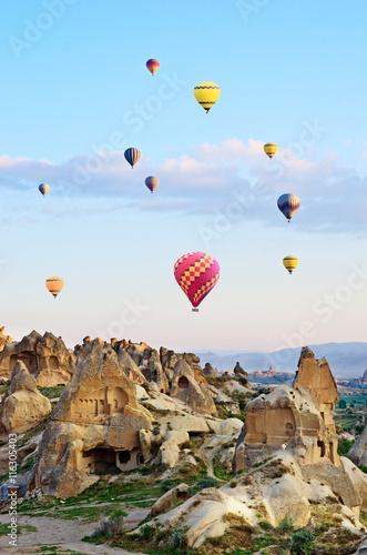 Hot air balloons over mountain landscape in Cappadocia