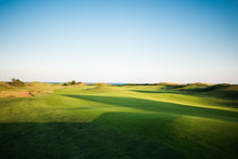 Beautiful Golf Course With Sand Traps And Sea In The Background At Sunset