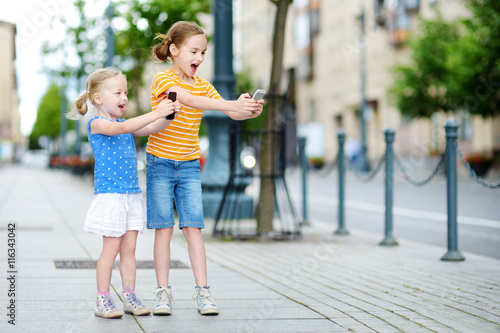 Two cute little sisters playing outdoor mobile game on their smart phones Canvas Print