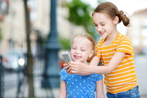 Photo  Two cute little sisters playing outdoor mobile game on their smart phones