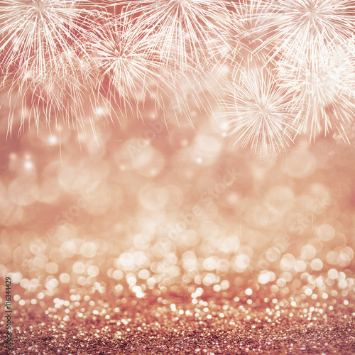 defocused rose gold fireworks and blurred bokeh at new year and copy space abstract background