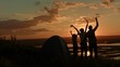 Young family - father, mother and son in camping - stands on high hill at summer sunset and have happy, silhouette