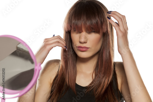 Photo  young woman adjusts her bangs on the mirror