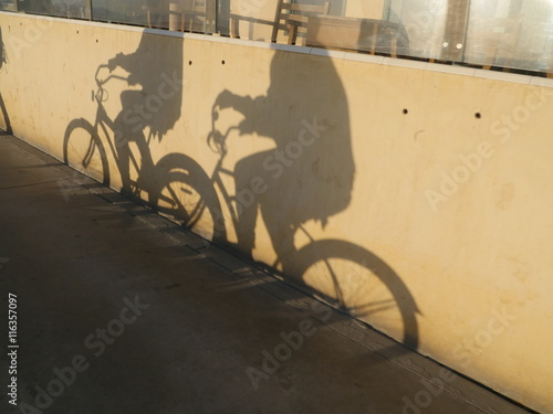 Staande foto Fiets Two people riding bikes. Their shadows on wall.