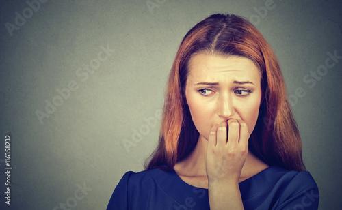 Fotografie, Obraz  Nervous woman biting her fingernails craving something or anxious