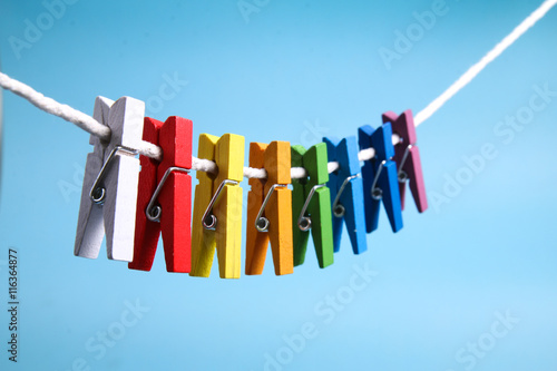Obraz na plátně  String of colorful clothes pegs on line against blue background
