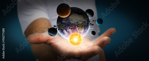 Businessman holding solar system in his hand